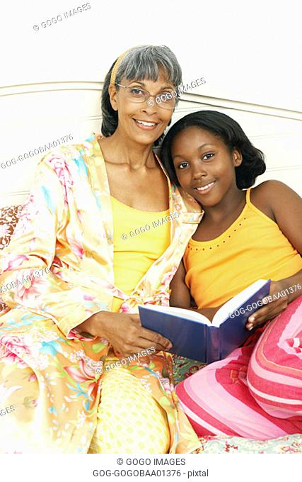 Middle-aged African woman reading with daughter