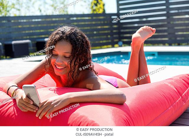 Girl lying on poolside cushion reading smartphone texts, Cassis, Provence, France