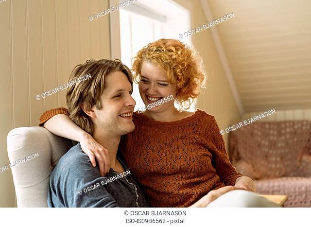 Woman sitting on man's lap smiling