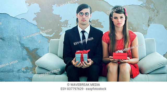 Composite image of unsmiling geeky couple with gift