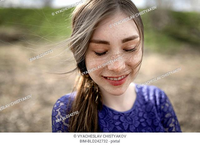 Wind blowing hair of smiling Caucasian woman