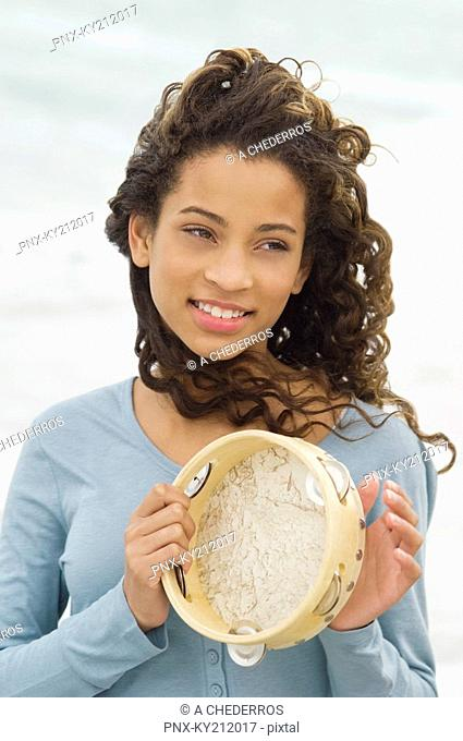 Close-up of a girl playing a tambourine