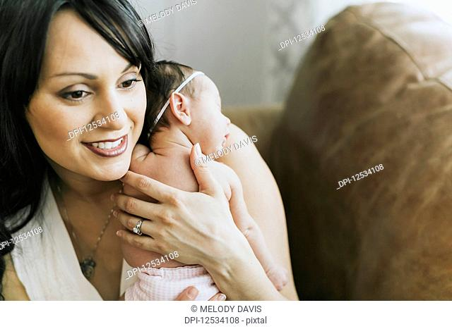 Newborn baby in mother's arms at home; Surrey, British Columbia, Canada