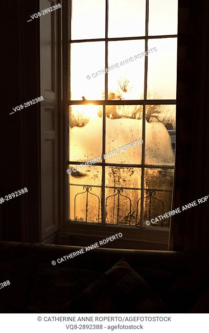 Golden sunrise through steamy C18th sash windows with decorative wooden shutters and iron work balcony, Bristol, England, UK