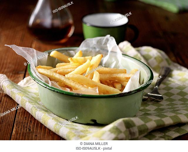French fries in vintage bowl on tea towel, with vinegar bottle