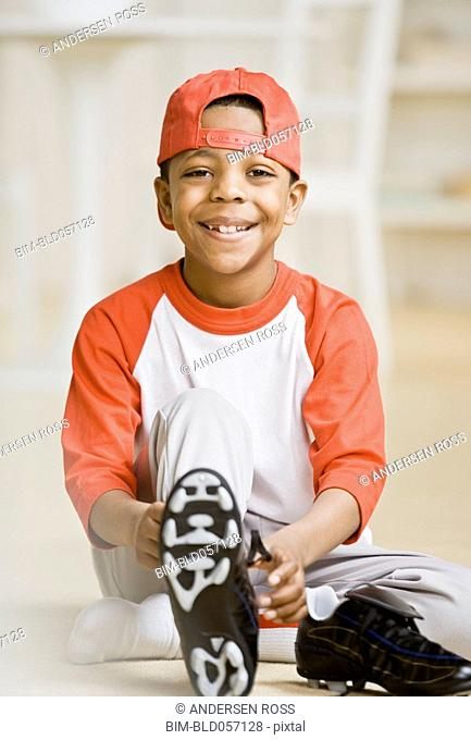 Mixed Race boy tying sports shoes