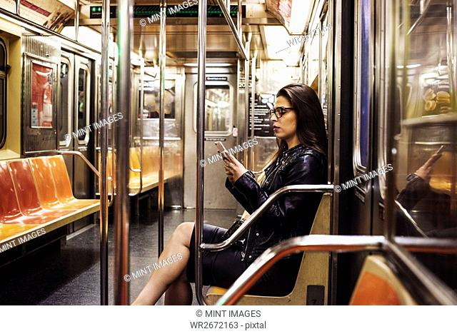 A woman sitting in a metro subway carriage looking at her cellphone