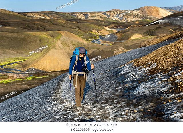 Female hiker walking on a snow field, rhyolite mountains covered with ash and snow on the Laugavegur hiking trail, Landmannalaugar Hrafntinnusker