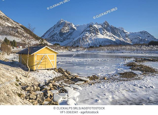 Yellow cabin with snowcapped mountains in the background. Vestpollen, Nordland county, Northern Norway region, Norway
