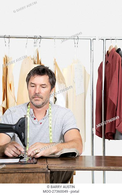 Male dressmaker stitching cloth on sewing machine with clothes rack in background