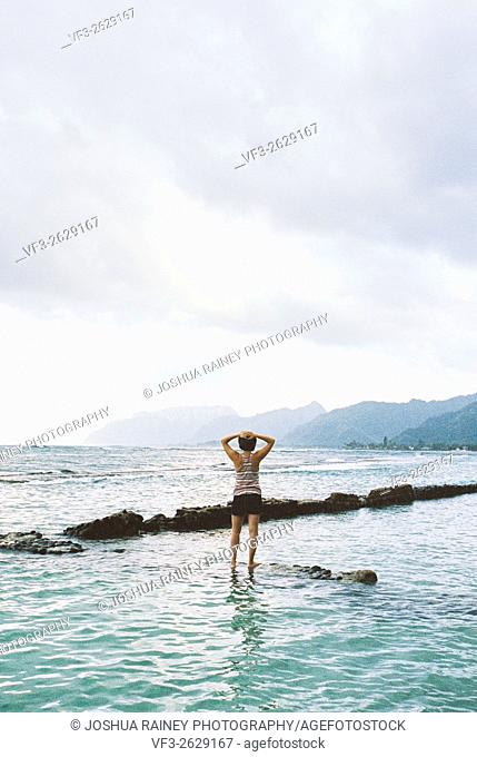 Portrait of a woman standing on rocks with her back to the camera while in the water in Oahu Hawaii