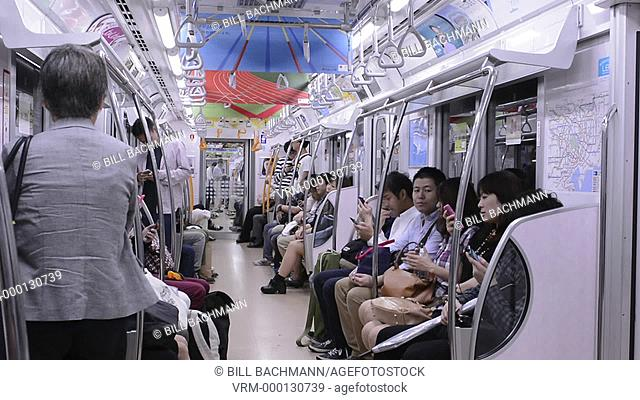 Tokyo Japan crowds subway car with locals going to work in crowded transportation of train cabin sitting relaxing