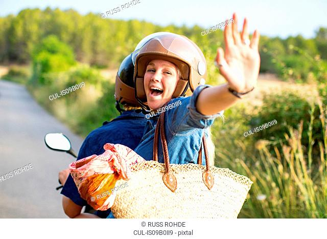 Young woman riding pillion on rural road waving, Majorca, Spain