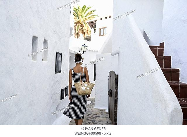 Spain, Menorca, Binibequer, back view of woman walking in an alley
