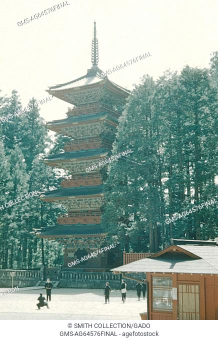 Japanese pagoda style temple set among trees, tourists standing in front of the template, one tourist posing for a photograph, Japan, 1951
