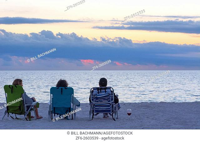 Bonita Beach Florida near Naples tourists relaxing at sunset on Gulf of Mexico beach with wine MR-1