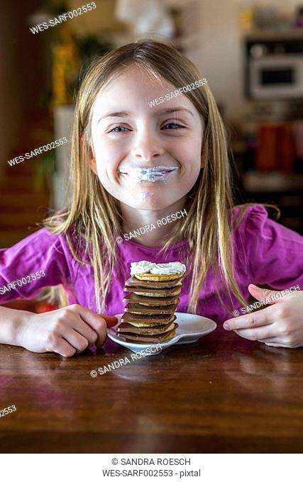 Portrait of happy girl with whipped cream on her lips and a stack of mini pancakes with chocolate