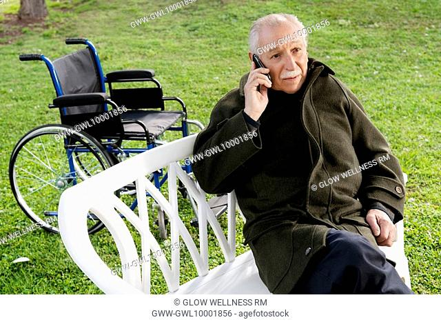 Man sitting on a chair and talking on a mobile phone