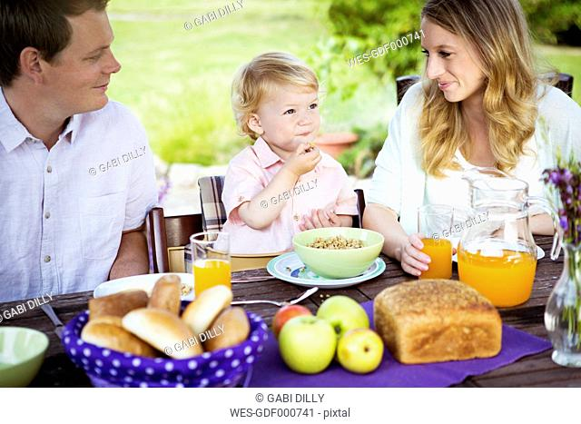 Happy family sitting at breakfast table