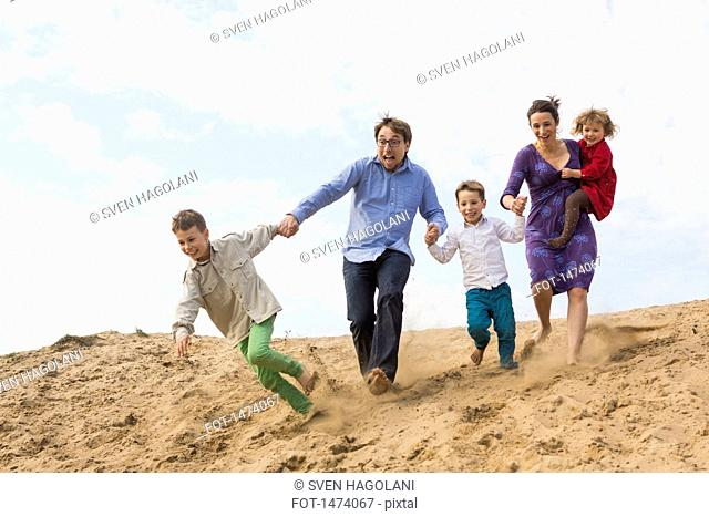 Cheerful family holding hands while running on sand dune against sky