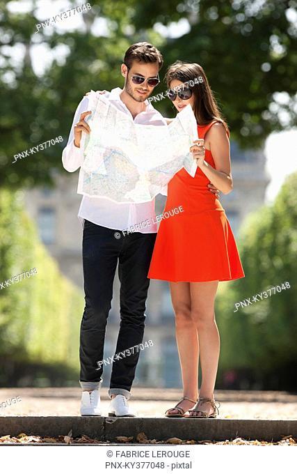 Couple reading a map in a garden, Terrasse De l'Orangerie, Jardin des Tuileries, Paris, Ile-de-France, France