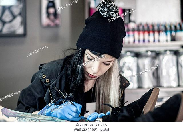 Female tattoo artist tattooing a leg