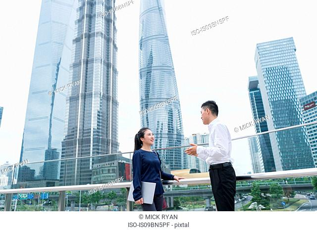 Young businesswoman and man talking in city financial district, Shanghai, China