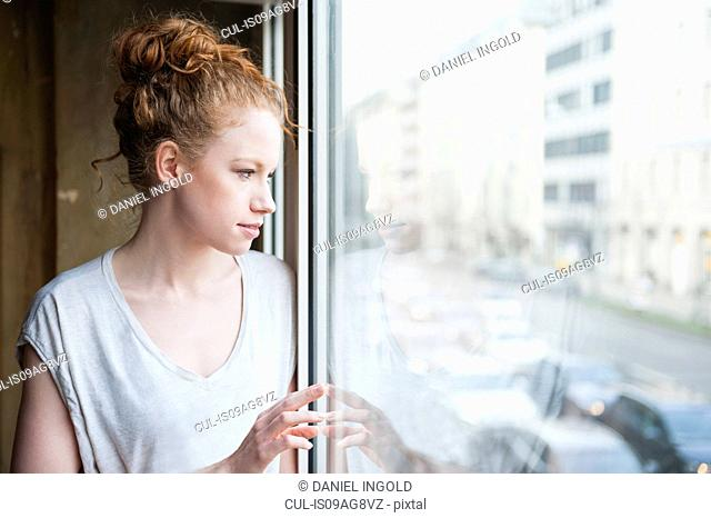 Young woman looking out of window at street