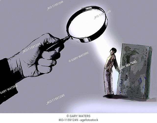 Hand holding magnifying glass over man hiding money