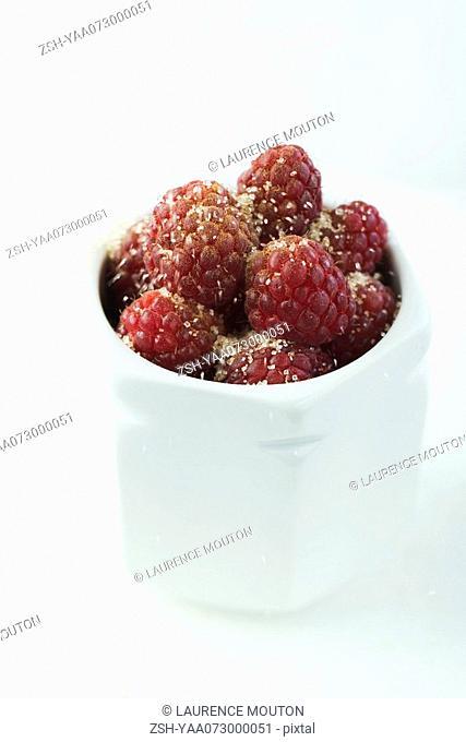 Raspberries sprinkled with sugar in porcelain jar