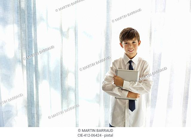 Boy in shirt and tie holding tablet computer