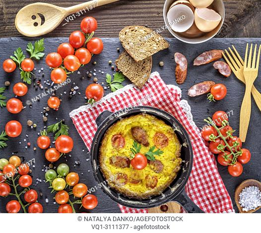 black round frying pan with fried omelette, next to fresh ripe red cherry tomatoes, top view
