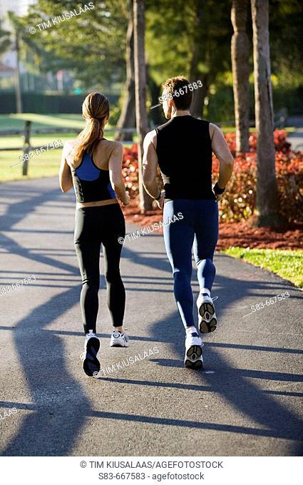 Man an woman jogging down a path
