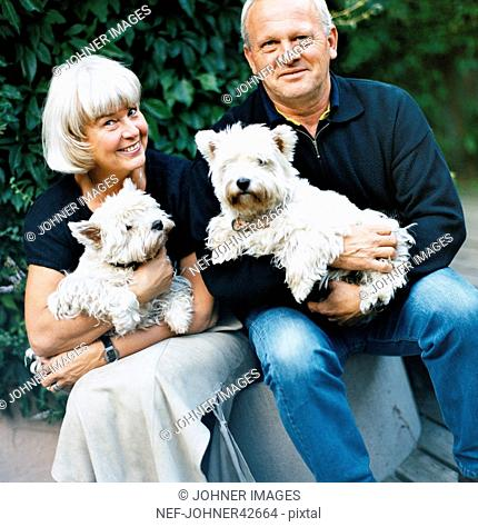 Elderly couple with dog in her arms