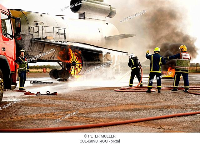 Firemen training, spraying water at mock airplane engine