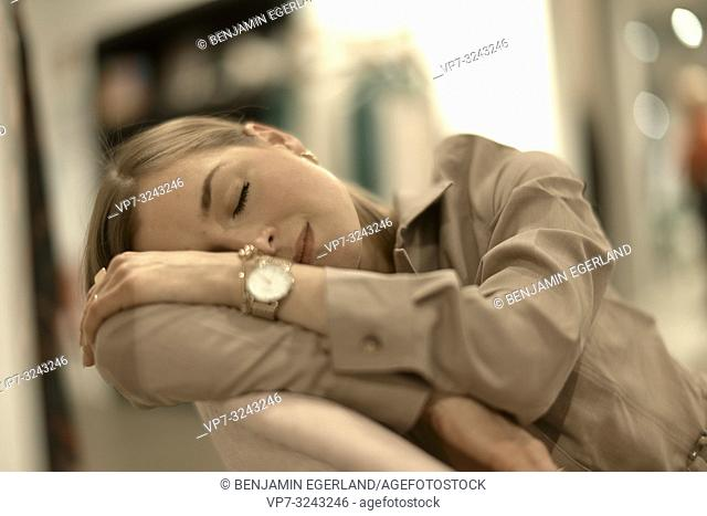 exhausted fashionable woman leaning on armchair, sleepy, closed eyes, tired, relaxing, in Munich, Germany