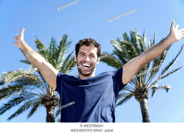 Spain, Mid adult man pretending to fly against palm tree