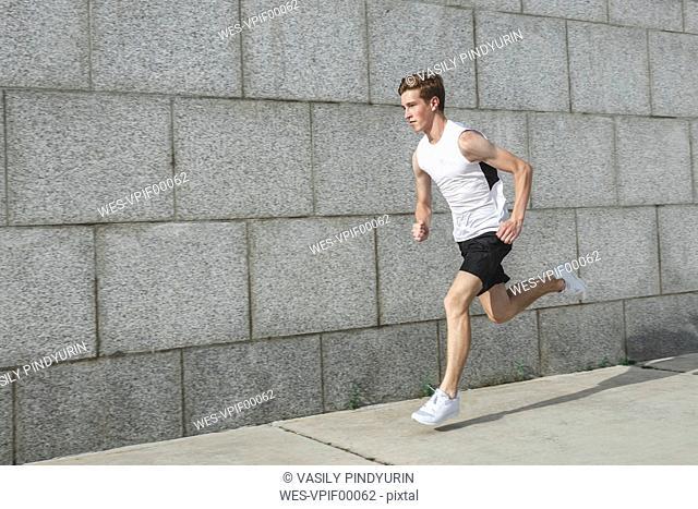 Young man running along wall