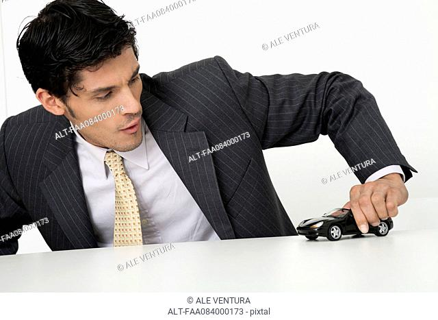 Mid-adult businessman playing with toy car