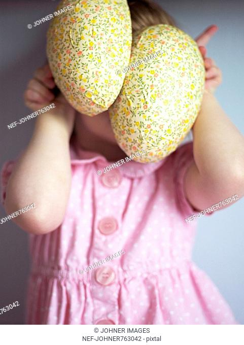 Girl in a pink dress holding two Easter eggs, Sweden