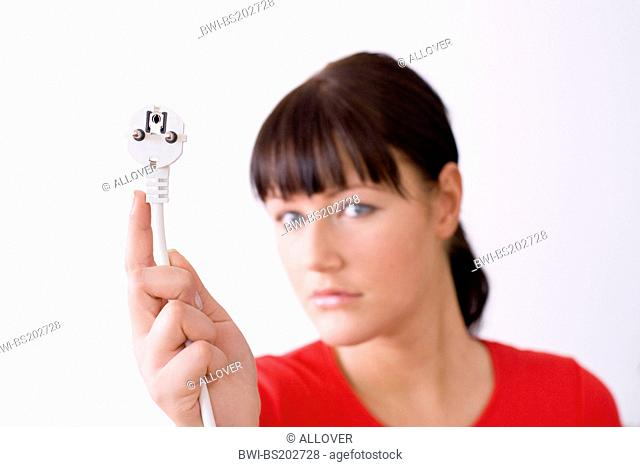 portrait of a darkhaired young woman with a plug in her hand