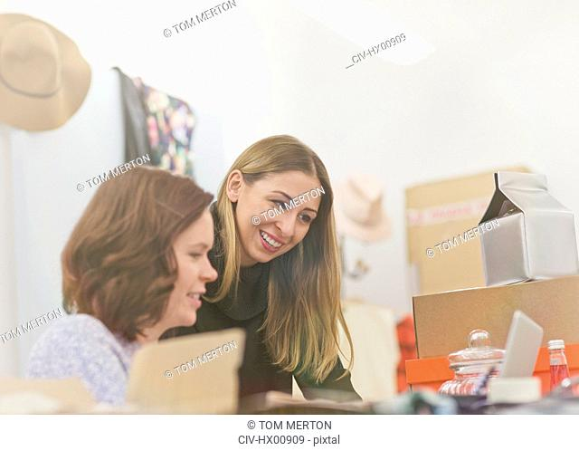 Smiling fashion buyers working at laptop in office