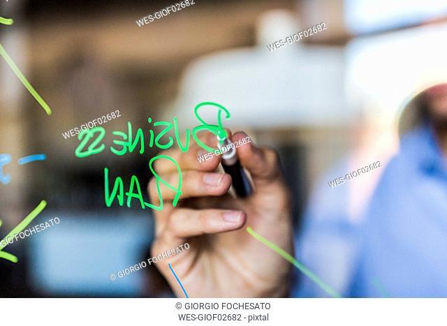 Businessman writing on glass wall