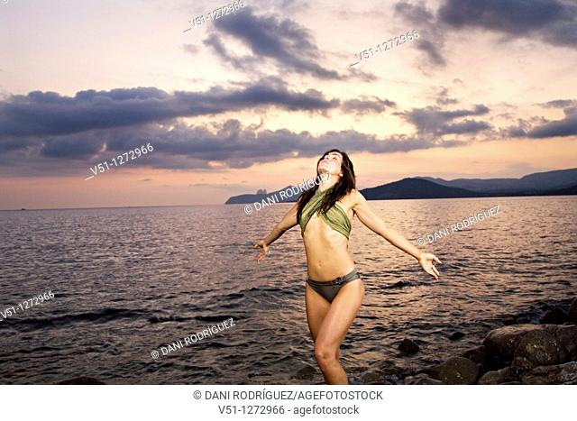 Brunette woman in bikini by the sea at sunset