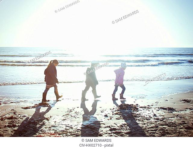 Brother and sisters in warm clothing walking in wet sand on sunny beach