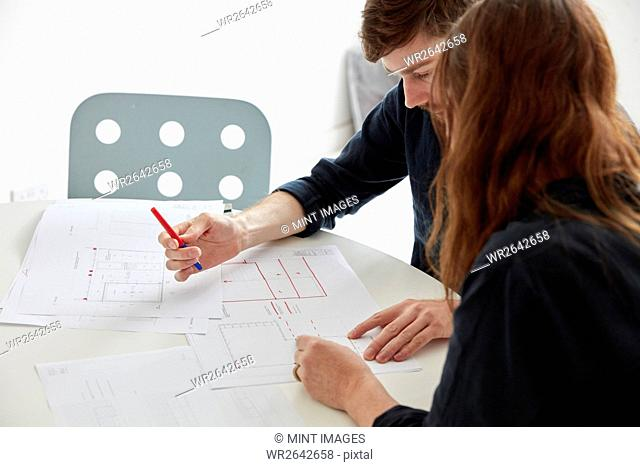 A modern office. Two people at a meeting discussing plans and drawings, Architectural drawings