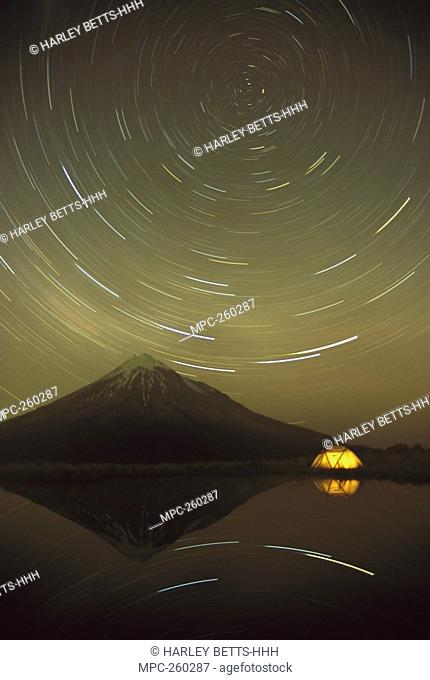Star trails around the south celestial pole in the evening sky over the Pouakai Range, Egmont National Park, New Zealand