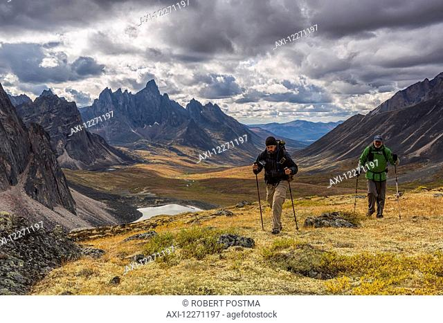 Hikers walking along a ridge in Tombstone Territorial Park in autumn, with Tombstone Valley and Tombstone Mountain in the distance; Yukon, Canada