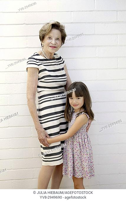 Five year old girl standing next to her great grandmother