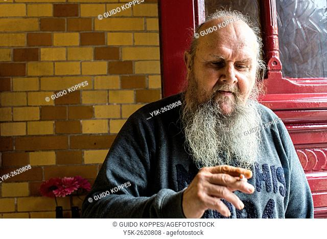 Tilburg, Netherlands. Senior adult male wearing a beard smoking a cigerette near the entrance door to a cafe restaurant